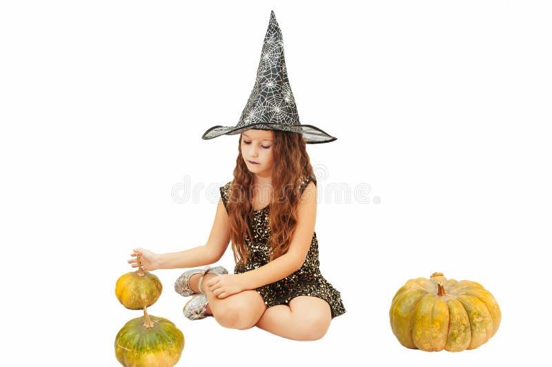 Menina com cabelo longo no equipamento da bruxa em Dia das Bruxas com abóboras, emocionalmente expressões da indicação imagem de stock