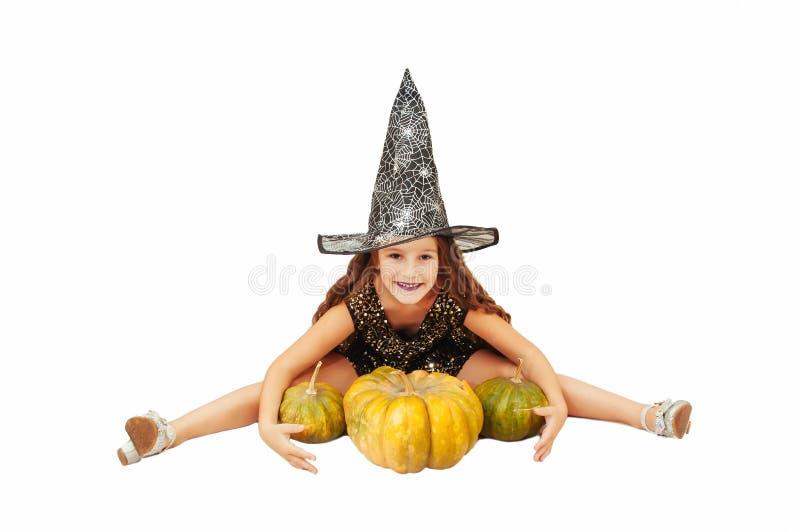 Menina com cabelo longo no equipamento da bruxa em Dia das Bruxas com abóboras, emocionalmente expressões da indicação imagens de stock