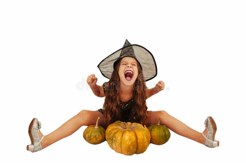 Menina com cabelo longo no equipamento da bruxa em Dia das Bruxas com abóboras, emocionalmente expressões da indicação foto de stock royalty free
