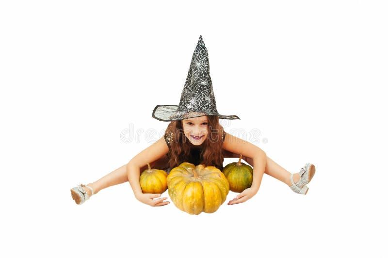 Menina com cabelo longo no equipamento da bruxa em Dia das Bruxas com abóboras, emocionalmente expressões da indicação imagens de stock royalty free