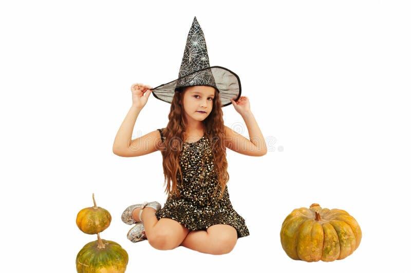 Menina com cabelo longo no equipamento da bruxa em Dia das Bruxas com abóboras, emocionalmente expressões da indicação fotografia de stock