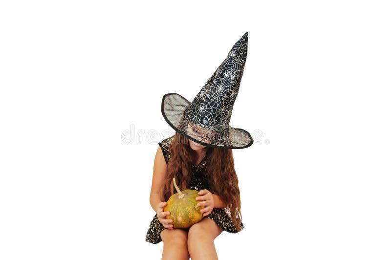 Menina com cabelo longo no equipamento da bruxa em Dia das Bruxas com abóboras, emocionalmente expressões da indicação fotos de stock