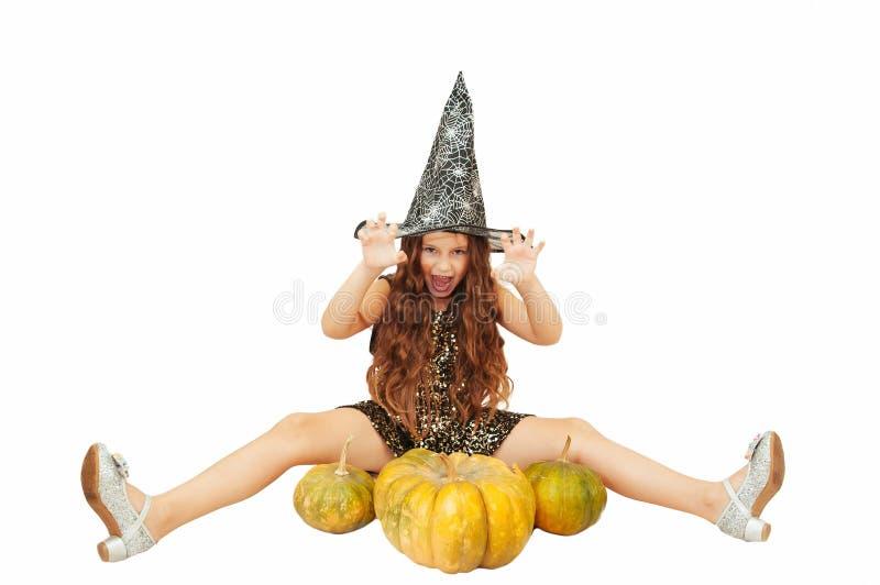 Menina com cabelo longo no equipamento da bruxa em Dia das Bruxas com abóboras, emocionalmente expressões da indicação imagem de stock royalty free