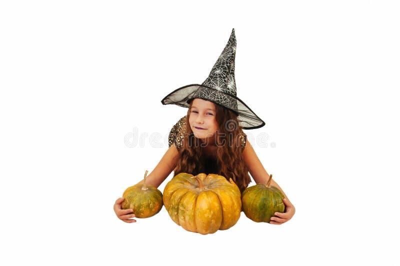 Menina com cabelo longo no equipamento da bruxa em Dia das Bruxas com abóboras, emocionalmente expressões da indicação fotografia de stock royalty free