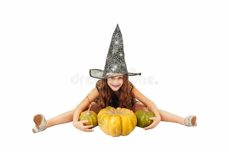 Menina com cabelo longo no equipamento da bruxa em Dia das Bruxas com abóboras, emocionalmente expressões da indicação fotos de stock royalty free