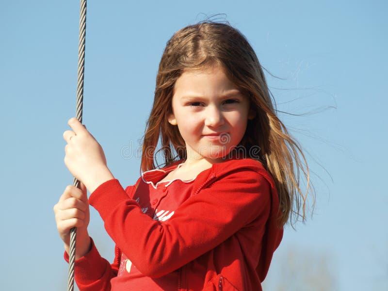 Menina com cabelo louro de fluxo em uma camiseta vermelha contra o céu azul imagem de stock