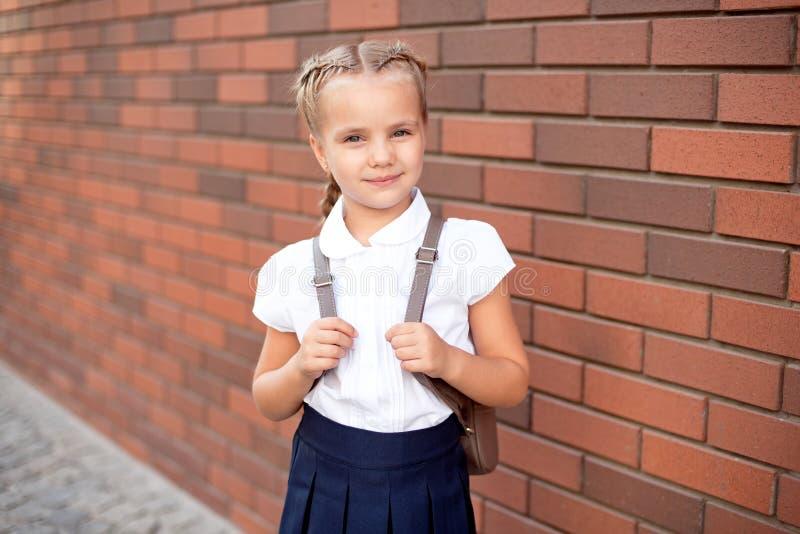 A menina com cabelo louro em uma camisa branca e em uma saia azul guarda uma placa vazia perto da parede superior fotos de stock royalty free