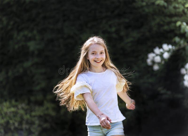 A menina com cabelo louro longo dança no jardim em um dia de mola bonito e é alegre foto de stock