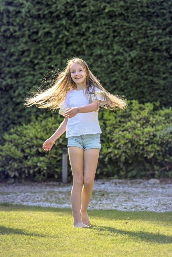 A menina com cabelo louro longo dança no jardim em um dia de mola bonito e é alegre fotografia de stock royalty free