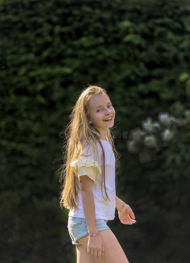 A menina com cabelo louro longo dança no jardim em um dia de mola bonito e é alegre imagem de stock