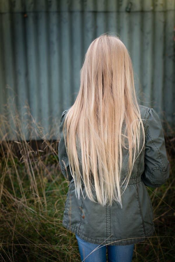 Menina com cabelo louro longo de trás por uma parede verde oxidada fotos de stock