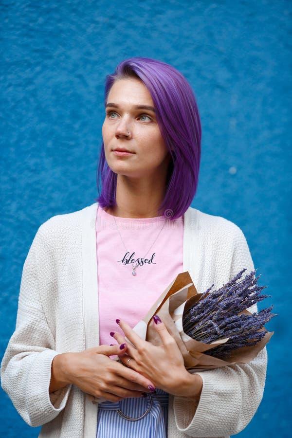 A menina com cabelo roxo guarda um ramalhete da alfazema foto de stock royalty free
