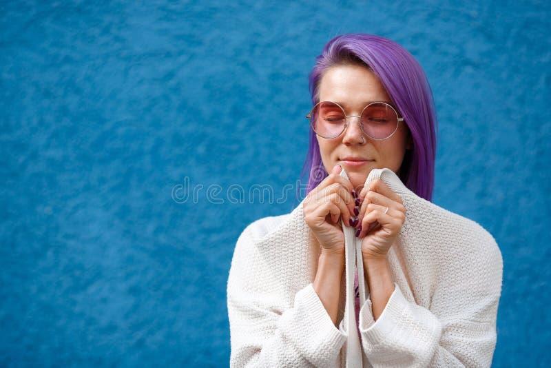 Menina com cabelo roxo no fundo azul imagens de stock