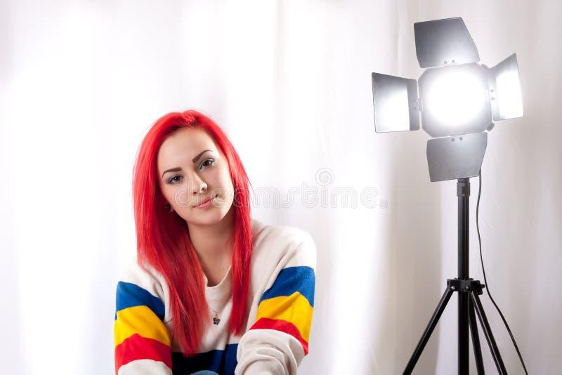 Menina com cabelo vermelho brilhante com um flash do estúdio imagem de stock