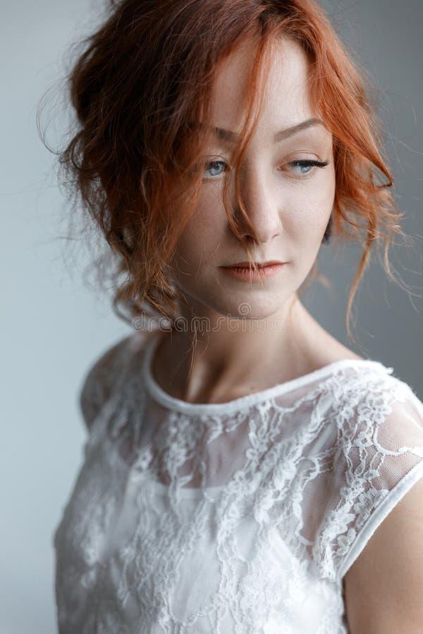 A menina com cabelo vermelho em um vestido branco olha afastado imagem de stock royalty free
