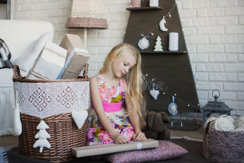 A menina com a caixa de presente nas mãos está feliz considera a preparação para o feriado, empacotando, caixas, Natal, ano novo, fotos de stock royalty free