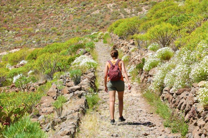 Menina com caminhadas da trouxa ao longo do trajeto da montanha Uma mulher está andando ao longo de uma estrada rochoso em Teneri fotografia de stock royalty free