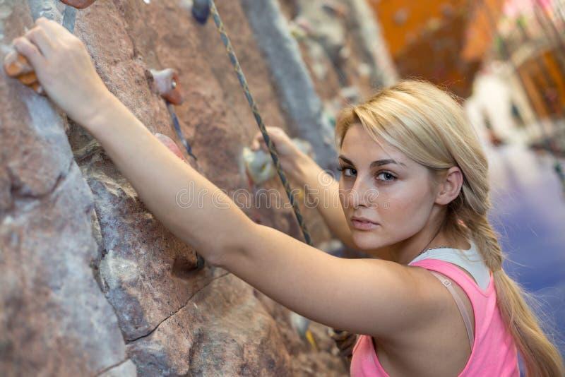 Menina com a cara concentrada com equipamento de escalada fotografia de stock