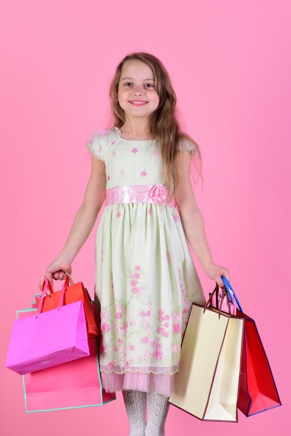 A menina com cara feliz guarda sacos de compras no fundo cor-de-rosa imagem de stock royalty free