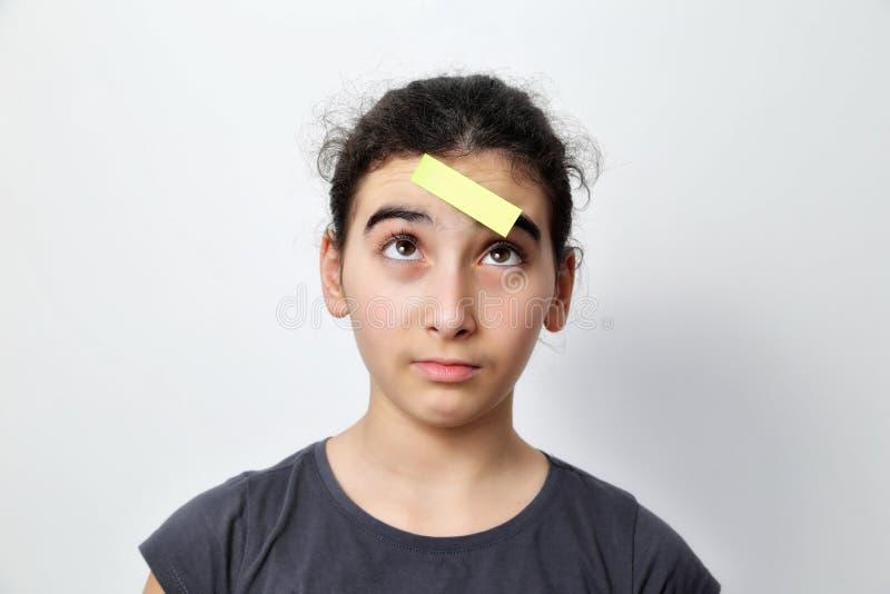 Menina com cargos do memorando em sua testa imagem de stock royalty free