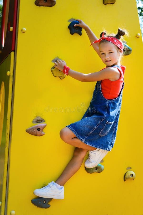 Menina com a cauda do penteado em escaladas do fato-macaco das calças de brim foto de stock royalty free