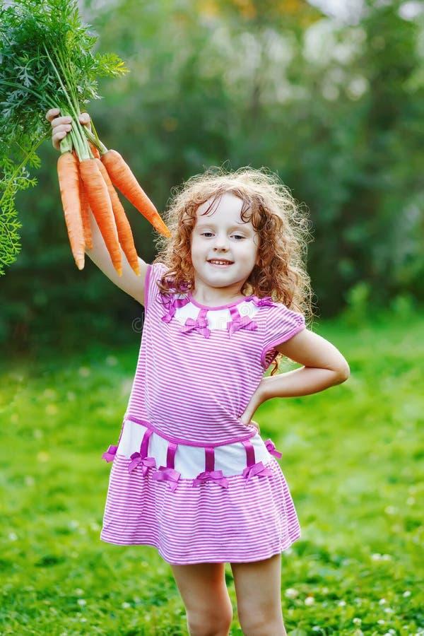 Menina com a cenoura amarela no jardim imagens de stock royalty free