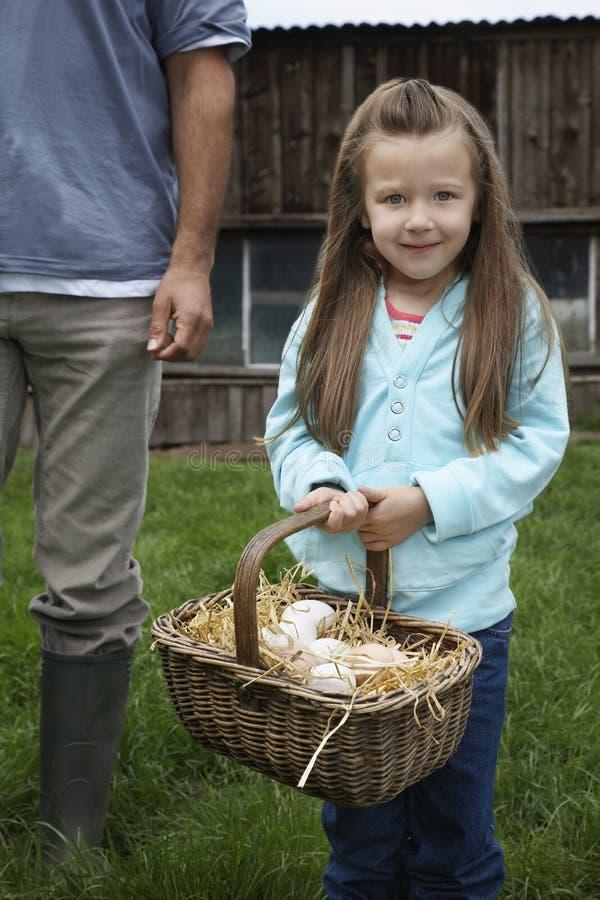 Menina com a cesta do ovo pelo pai colhido On Grassland fotografia de stock royalty free