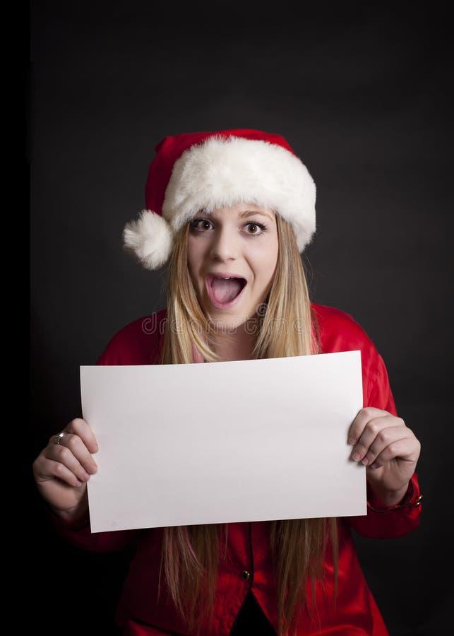 Menina com chapéu de Santa sobre e sinal em branco fotografia de stock royalty free