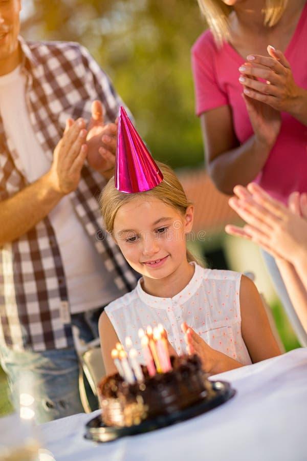 Menina com chapéu do partido e bolo de aniversário fotografia de stock royalty free
