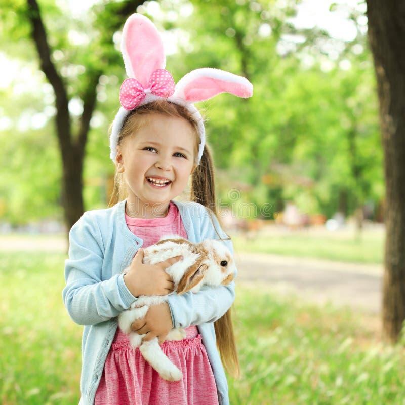 Menina com coelho adorável fora no dia ensolarado imagem de stock royalty free