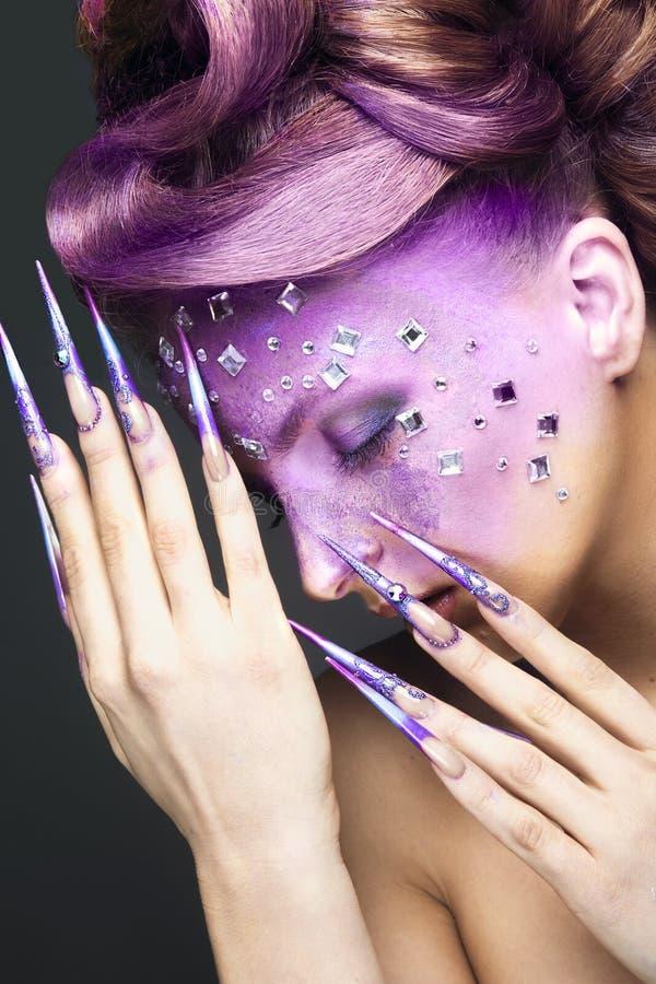 Menina com composição criativa roxa brilhante com cristais e os pregos longos Face da beleza imagens de stock