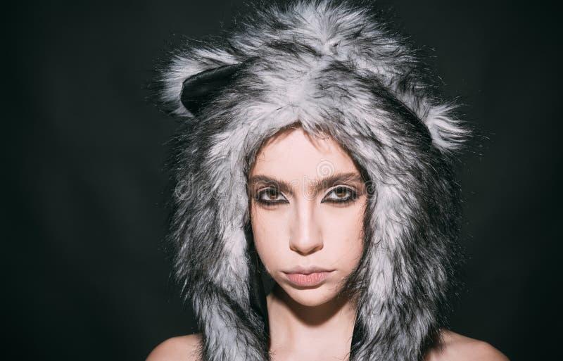 A menina com composição veste o chapéu forrado a pele macio com as orelhas como o gato Equipamento bonito da vaquinha Ideias do c foto de stock royalty free