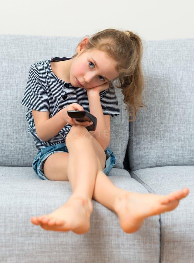 Menina com controlo a distância fotografia de stock royalty free