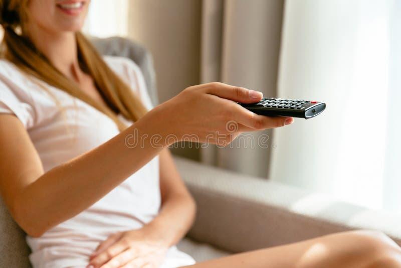 Menina com controlo a distância da tevê à disposição que olha a tevê em casa fotografia de stock royalty free