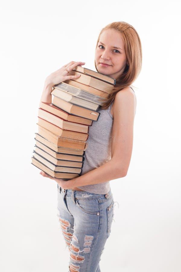 A menina com cor da pilha empilhou o livro no branco fotografia de stock