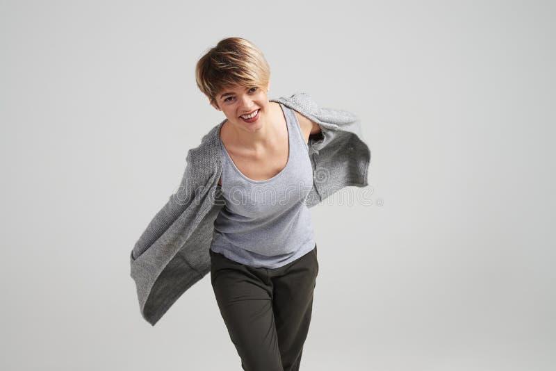 Menina com corte de cabelo curto no casaco de lã de fluxo que levanta no estúdio imagem de stock