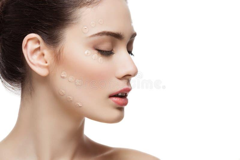 Menina com creme de fundação na cara imagem de stock