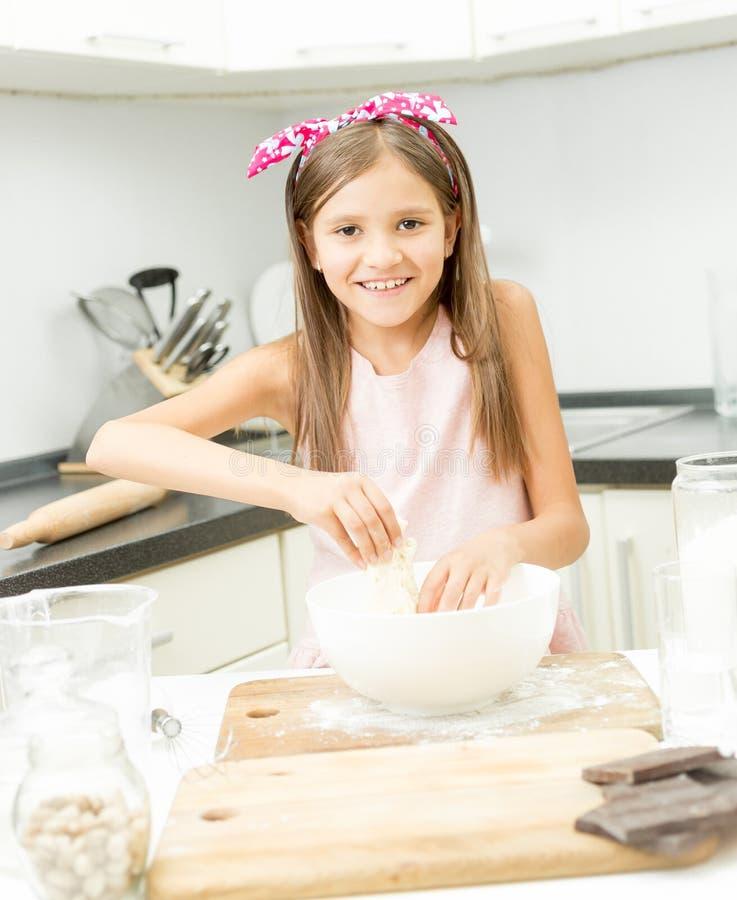 Menina com curva cor-de-rosa no cabelo que faz a massa na bacia grande foto de stock