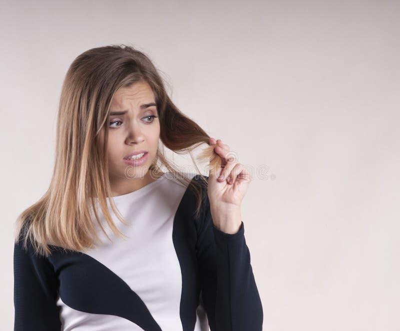 Menina com decepção da perplexidade do problema do cabelo da separação foto de stock