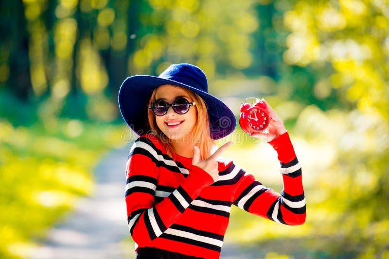 Menina com despertador vermelho em um parque foto de stock