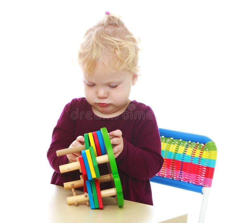 A menina com dois anos pequena senta-se em uma tabela e em jogos fotografia de stock royalty free
