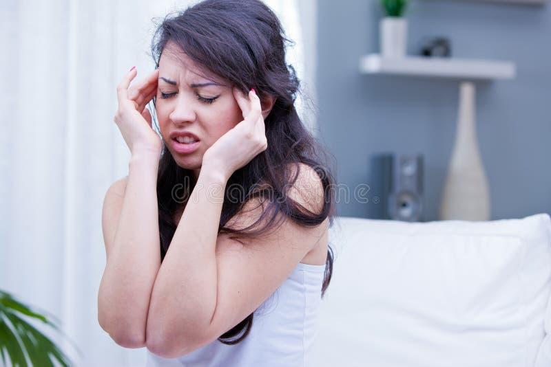 Menina com dor de cabeça dolorosa em sua sala de visitas fotos de stock royalty free