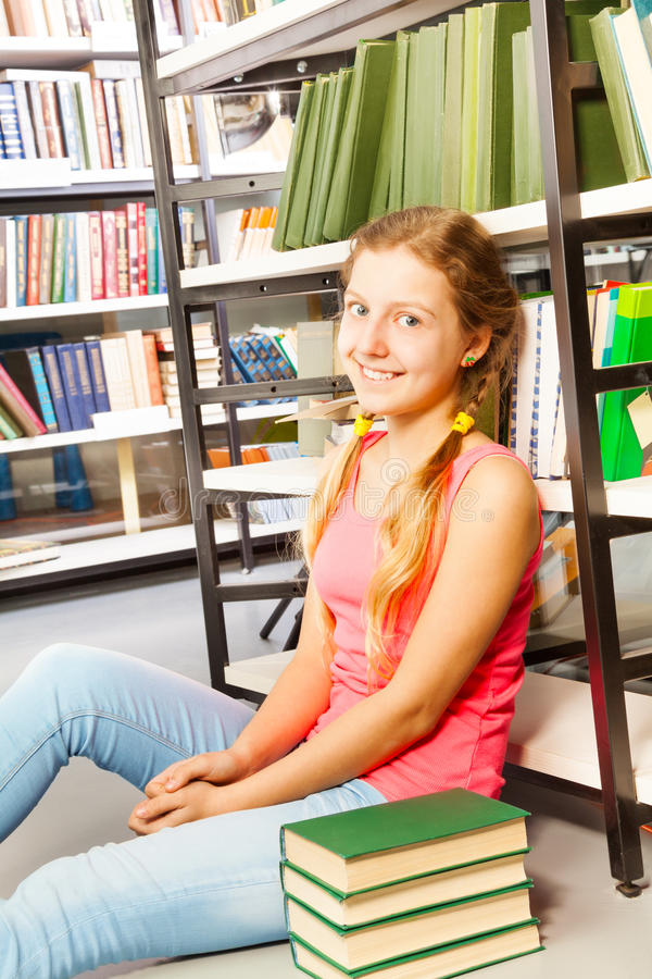 A menina com duas tranças senta-se no assoalho na biblioteca imagens de stock