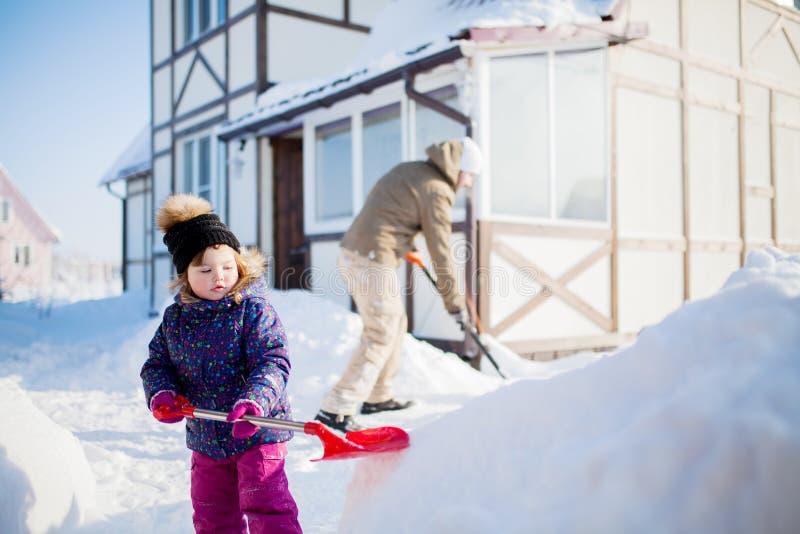 Menina com e seu pai que trabalha fora com uma pá da neve imagens de stock