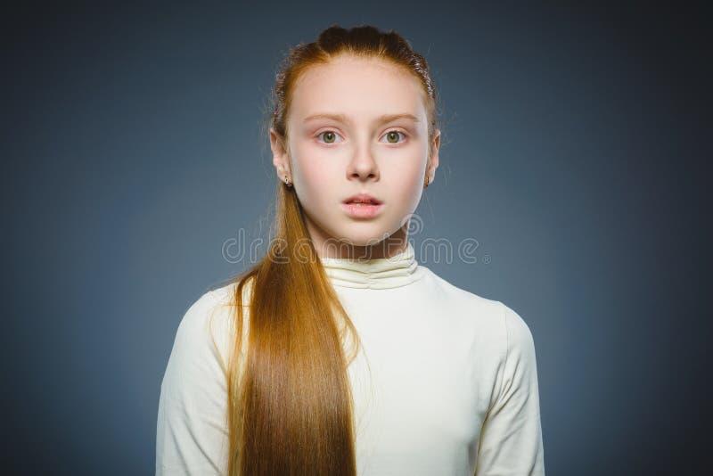 Menina com expressão surpreendida ao estar contra o fundo cinzento foto de stock royalty free