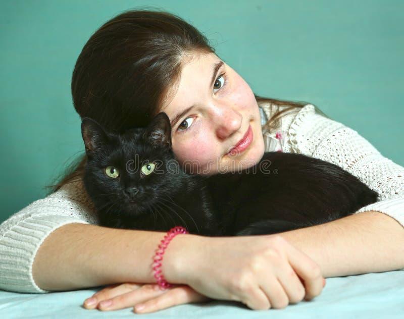Menina com fim do gato preto acima do retrato fotografia de stock