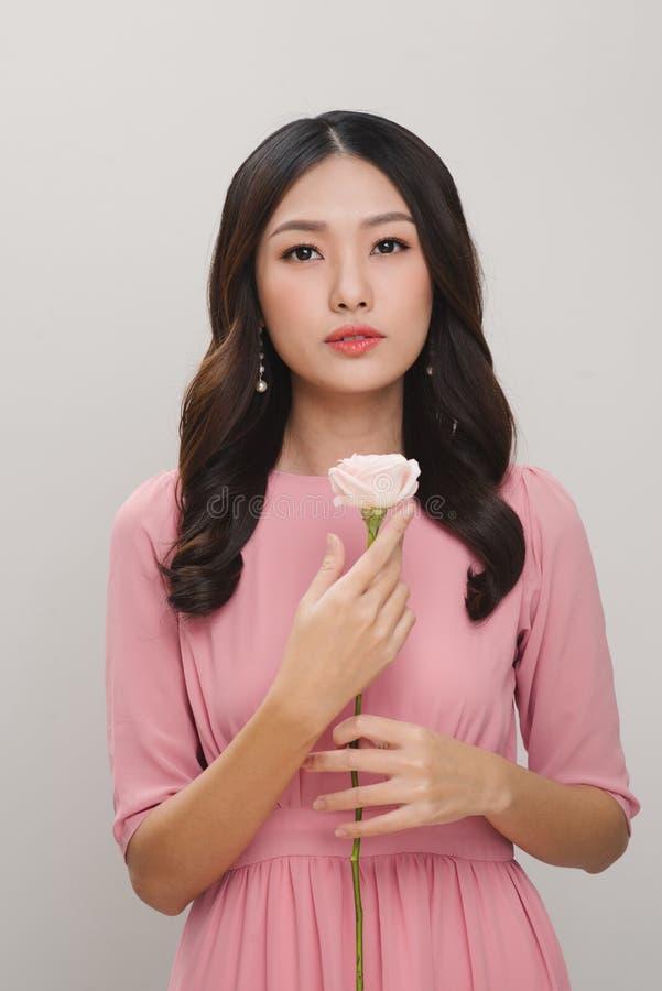 Menina com flor Jovem mulher bonita que guarda a rosa do vermelho e o SMI fotografia de stock royalty free
