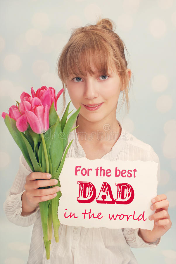 Menina com flores e cumprimentos para o paizinho imagens de stock