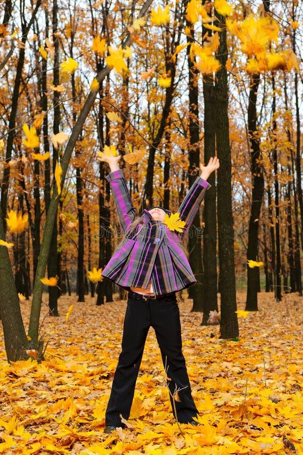 A menina com a floresta levantada do outono das mãos foto de stock