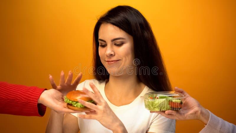 Menina com fome que escolhe o Hamburger em vez da salada, comida lixo barata contra a dieta saudável foto de stock royalty free